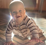 baby_crawling_sitting_floor_smiling_eyes_open_wide