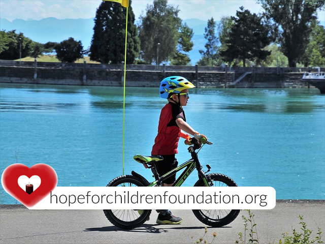 helping children_child_bike_water_lake